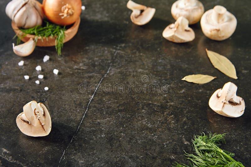 Ολόκληροι βολβός, μανιτάρια, άνηθος και σκόρδο σε ένα μαύρο πέτρινο Backgrou στοκ εικόνες