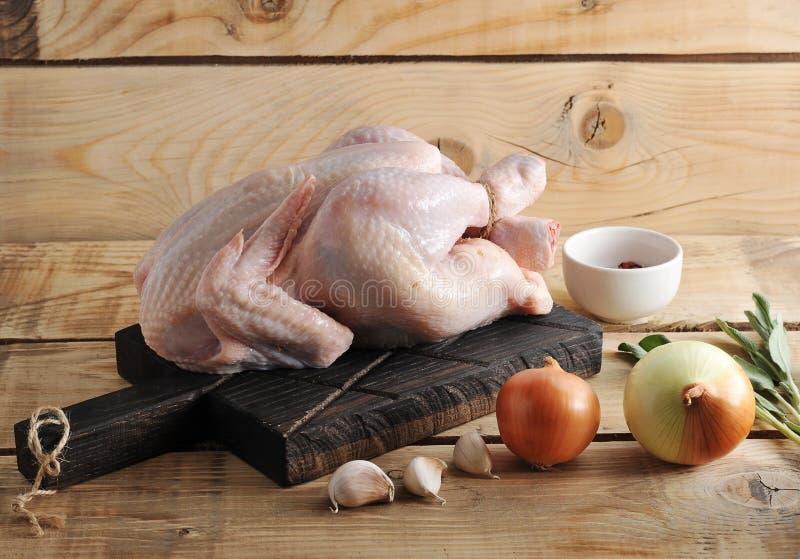 Ολόκληρο ακατέργαστο σφάγιο κοτόπουλου στην επιτροπή και τα καρυκεύματα στοκ εικόνα με δικαίωμα ελεύθερης χρήσης