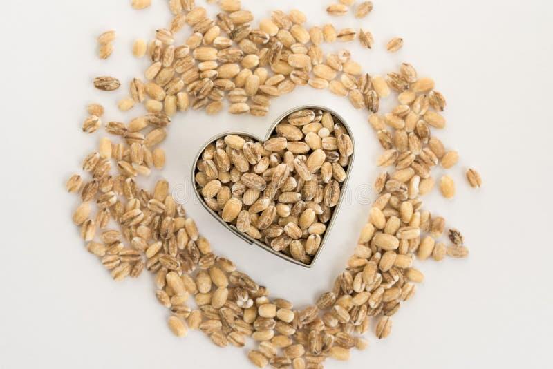 Ολόκληρο κριθάρι άλεσης σιταριού σε μια μορφή καρδιών στοκ φωτογραφία