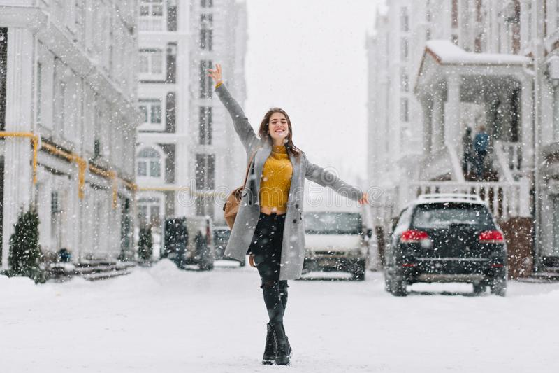 Ολόκληρο πορτρέτο του εμπνευσμένου θηλυκού προτύπου στη μοντέρνη τοποθέτηση παλτών με την ευχαρίστηση στη χειμερινή πόλη Υπαίθρια στοκ φωτογραφίες με δικαίωμα ελεύθερης χρήσης