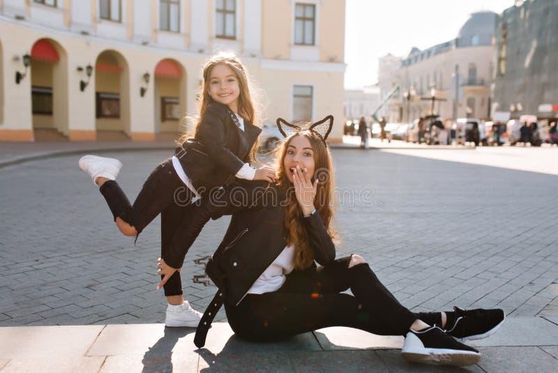 Ολόκληρο πορτρέτο του εύθυμου πηδώντας κοριτσιού στα άσπρα παπούτσια που θέτουν πρόθυμα μπροστά από το όμορφο κτήριο με έκπληκτος στοκ φωτογραφία με δικαίωμα ελεύθερης χρήσης