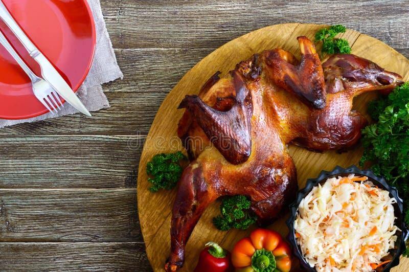 Ολόκληρο ψημένο ισιωμένο κοτόπουλο με μια χρυσή τριζάτη κρούστα με τα φρέσκα λαχανικά, τα χορτάρια και τη σαλάτα λάχανων σε έναν  στοκ φωτογραφίες με δικαίωμα ελεύθερης χρήσης