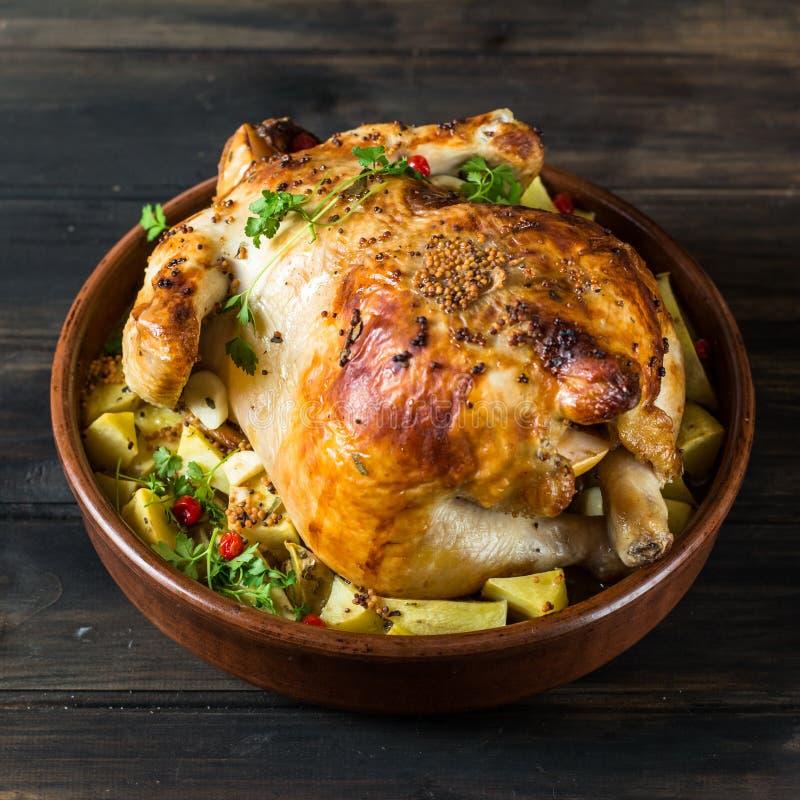 Ολόκληρο ψημένο κοτόπουλο με τα μανιτάρια και τις πατάτες σε ένα πιάτο ψησίματος σε έναν πίνακα Ψημένη Τουρκία Πιάτο Χριστουγέννω στοκ εικόνες