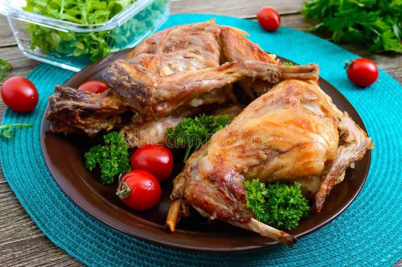 Ολόκληρο ψημένο κουνέλι με τα πράσινα και ντομάτες σε ένα πιάτο Νόστιμο διαιτητικό κρέας στοκ φωτογραφία