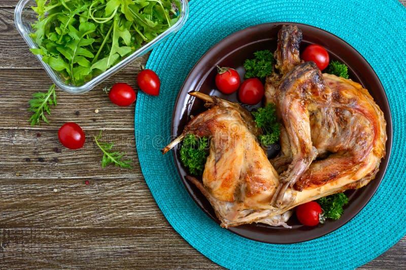 Ολόκληρο ψημένο κουνέλι με τα πράσινα και ντομάτες σε ένα πιάτο Νόστιμο διαιτητικό κρέας r στοκ φωτογραφία