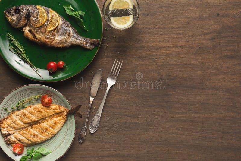 Ολόκληρο ψημένο στη σχάρα dorado και άσπρα ψάρια στον πίνακα στοκ εικόνες