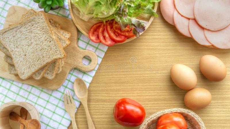 Σπιτικό να προετοιμαστεί προγευμάτων σάντουιτς Ολόκληρο ψωμί σίτου που συσσωρεύεται σε έναν ξύλινο τέμνοντα πίνακα Ντομάτες και μ στοκ εικόνες
