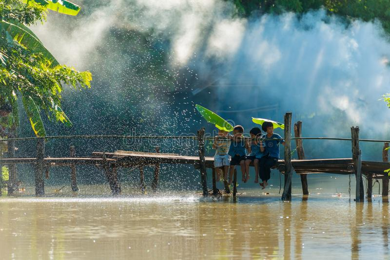 Ομάδα αγροτικών παιδιών που κάθονται μαζί στην ξύλινη γέφυρα στοκ φωτογραφία με δικαίωμα ελεύθερης χρήσης