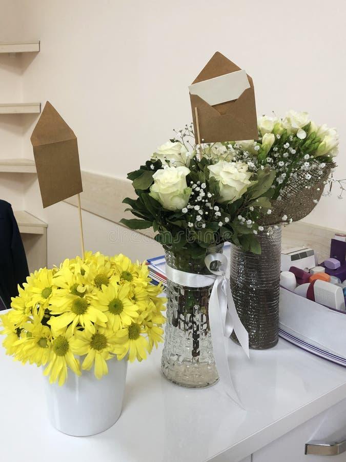 Ομάδα ανθοδεσμών λουλουδιών με τη ευχετήρια κάρτα στο γραφείο γραφείων στοκ εικόνες