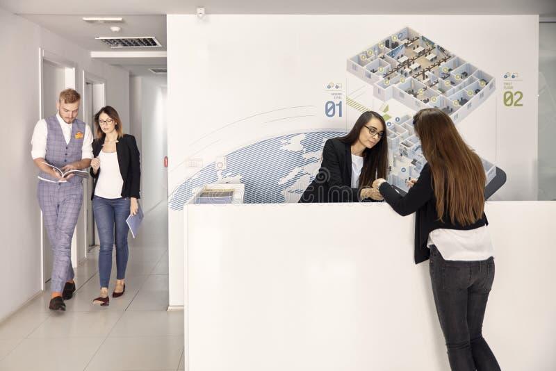 Ομάδα ανθρώπων, δύο άνθρωποι που περπατά, δύο γυναίκες που εξετάζουν τα έγγραφα στο σύγχρονο διάδρομο γραφείων στοκ εικόνα