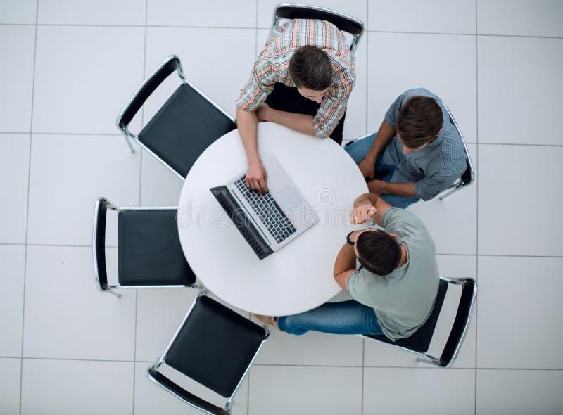 Ομάδα ανθρώπων με τις συσκευές που κάθεται σε μια διάσκεψη στρογγυλής τραπέζης στοκ φωτογραφία