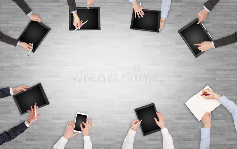 Ομάδα ανθρώπων με τις συσκευές στα χέρια που διοργανώνουν τη συζήτηση γραφείων και που λειτουργούν στα lap-top, ταμπλέτες στην ομ στοκ εικόνες