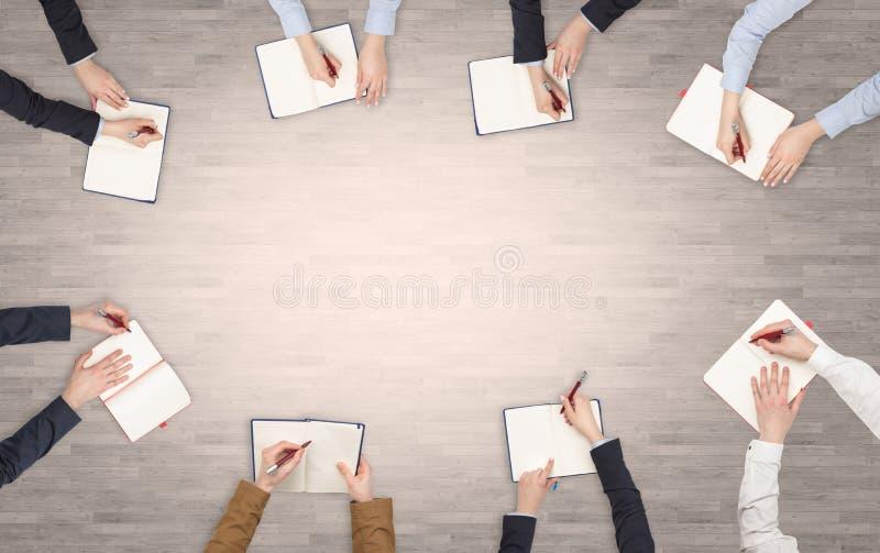 Ομάδα ανθρώπων με τις συσκευές στα χέρια που διοργανώνουν τη συζήτηση γραφείων και που λειτουργούν στα lap-top, ταμπλέτες στην ομ στοκ φωτογραφία με δικαίωμα ελεύθερης χρήσης