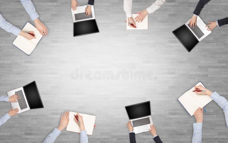 Ομάδα ανθρώπων με τις συσκευές στα χέρια που διοργανώνουν τη συζήτηση γραφείων και που λειτουργούν στα lap-top, ταμπλέτες στην ομ στοκ φωτογραφίες