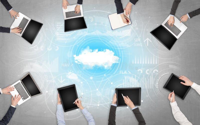 Ομάδα ανθρώπων με τις συσκευές στα χέρια που λειτουργούν στα lap-top και τις ταμπλέτες με τη σε απευθείας σύνδεση έννοια ομαδικής στοκ εικόνες