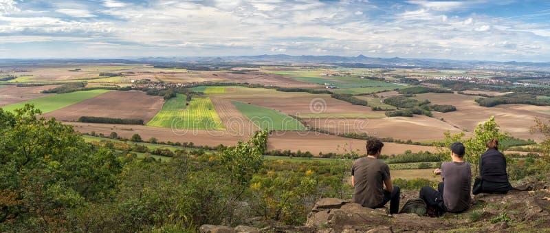 Ομάδα ανθρώπων που κοιτούν το αγροτικό τοπίο με χωριά, χωράφια και βουνά στο παρασκήνιο στοκ εικόνες