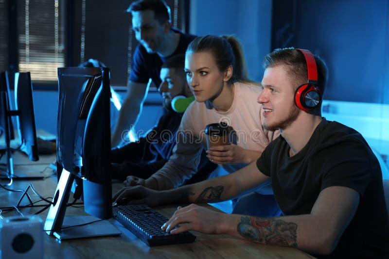 Ομάδα ανθρώπων που παίζει τα τηλεοπτικά παιχνίδια στον καφέ στοκ φωτογραφία