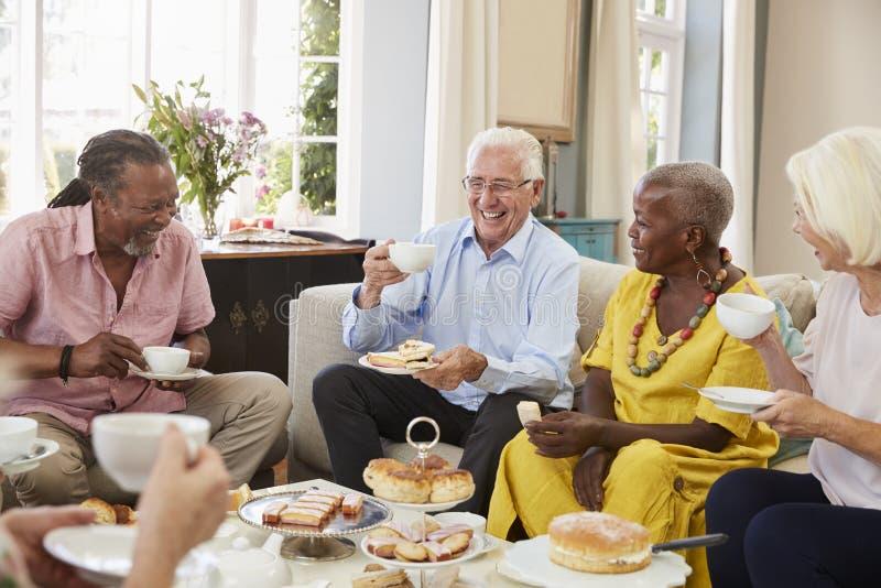 Ομάδα ανώτερων φίλων που απολαμβάνουν το τσάι απογεύματος στο σπίτι από κοινού στοκ φωτογραφίες