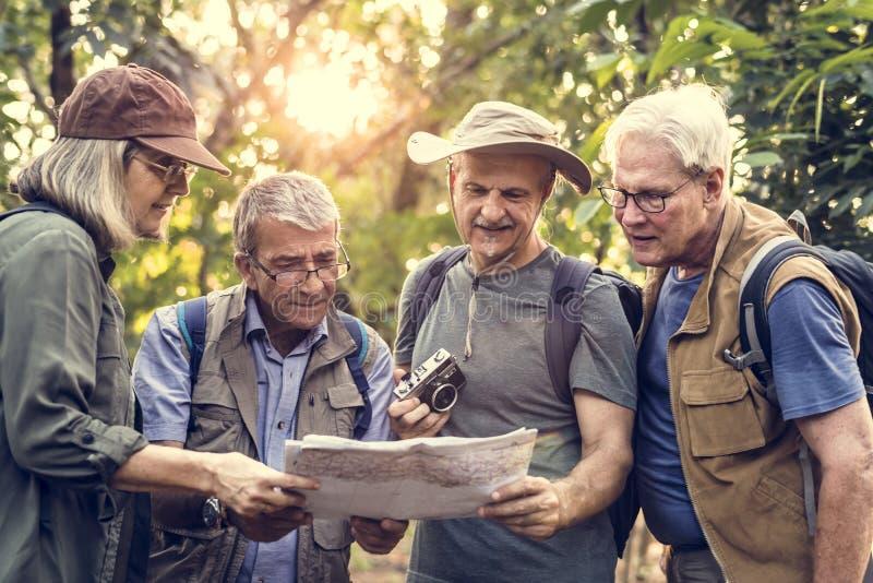 Ομάδα ανώτερων trekkers που ελέγχει έναν χάρτη για την κατεύθυνση στοκ φωτογραφία με δικαίωμα ελεύθερης χρήσης