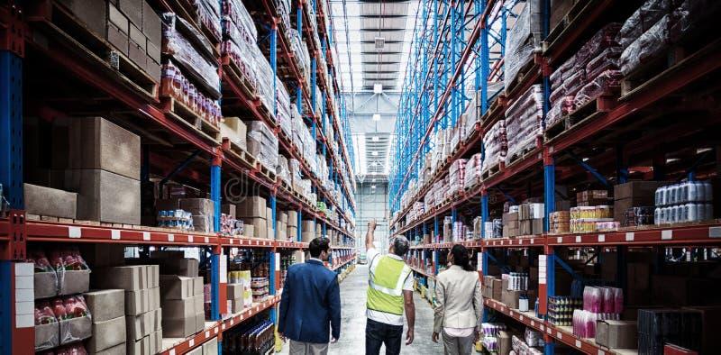Ομάδα αποθηκών εμπορευμάτων που συζητά περπατώντας στην αποθήκη εμπορευμάτων στοκ φωτογραφίες