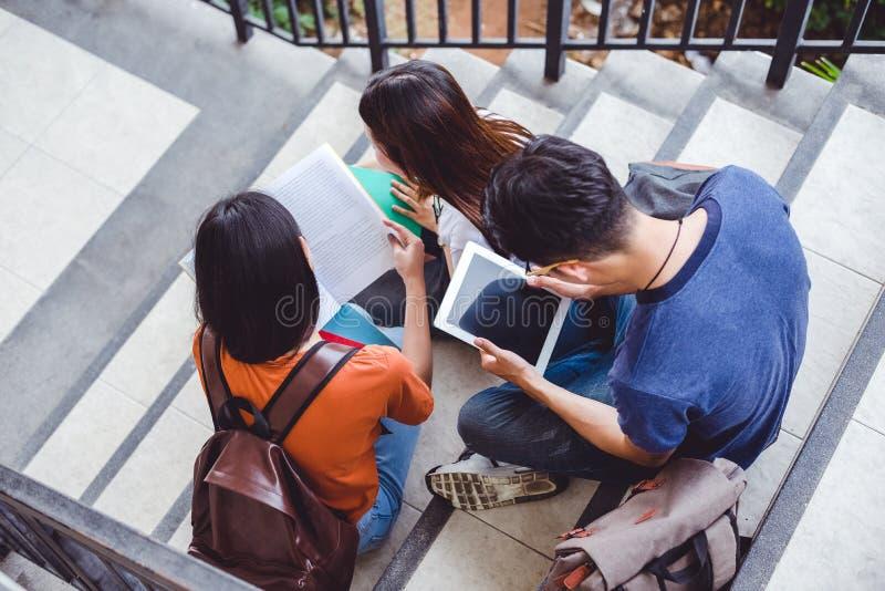 Ομάδα ασιατικού φοιτητή πανεπιστημίου που χρησιμοποιούν την ταμπλέτα και κινητού τηλεφώνου έξω από την τάξη Έννοια εκμάθησης ευτυ στοκ εικόνα