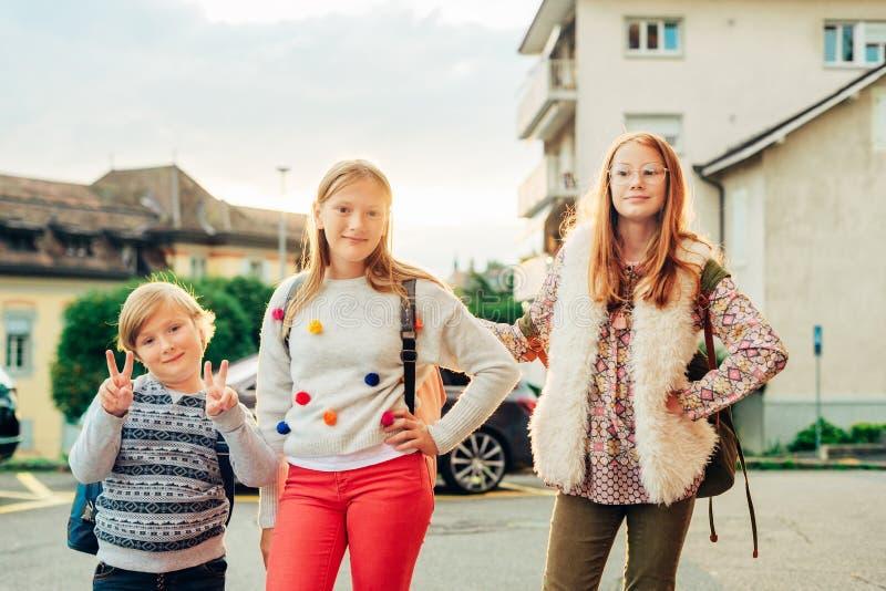 Ομάδα 3 αστείων παιδιών με τα σακίδια πλάτης, 2 μαθητριών και ενός preschooler στοκ φωτογραφίες με δικαίωμα ελεύθερης χρήσης