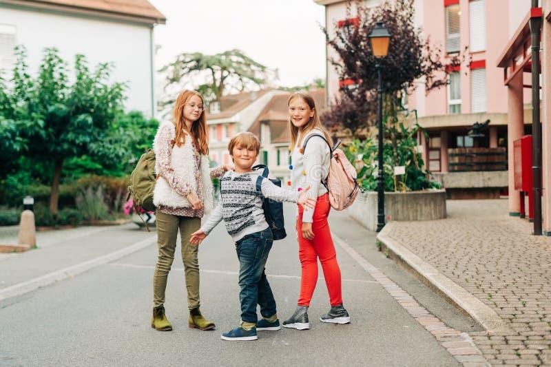 Ομάδα 3 αστείων παιδιών με τα σακίδια πλάτης, 2 μαθητριών και ενός preschooler στοκ φωτογραφία
