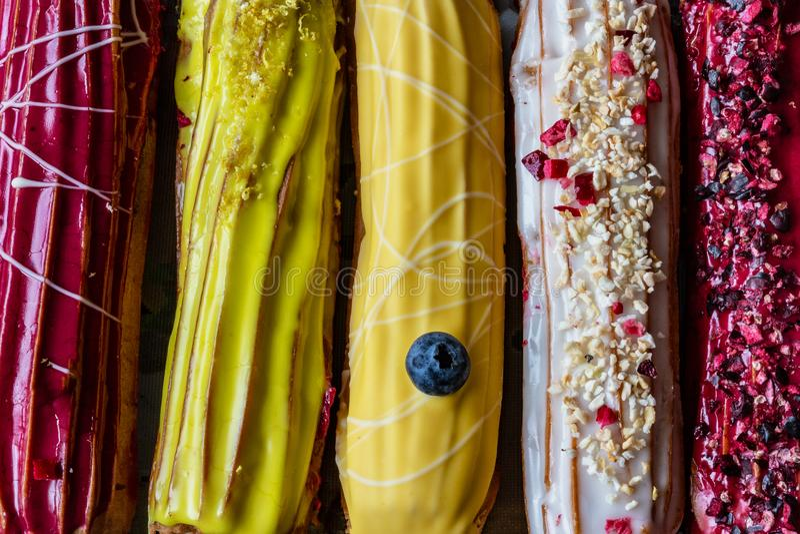 Ομάδα γαλλικού κέικ ECLAIR επιδορπίων με άσπρο κίτρινο και κόκκινο creme και τη λάμποντας διακόσμηση στοκ εικόνες