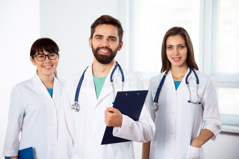 Ομάδα γιατρών που εξετάζουν τη κάμερα και το χαμόγελο στοκ φωτογραφίες