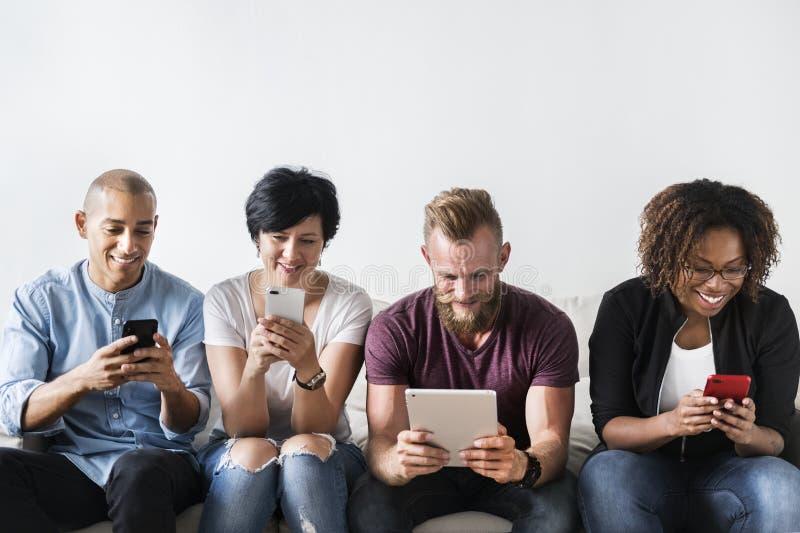 Ομάδα διαφορετικών ανθρώπων που χρησιμοποιούν τις ψηφιακές συσκευές στοκ εικόνα