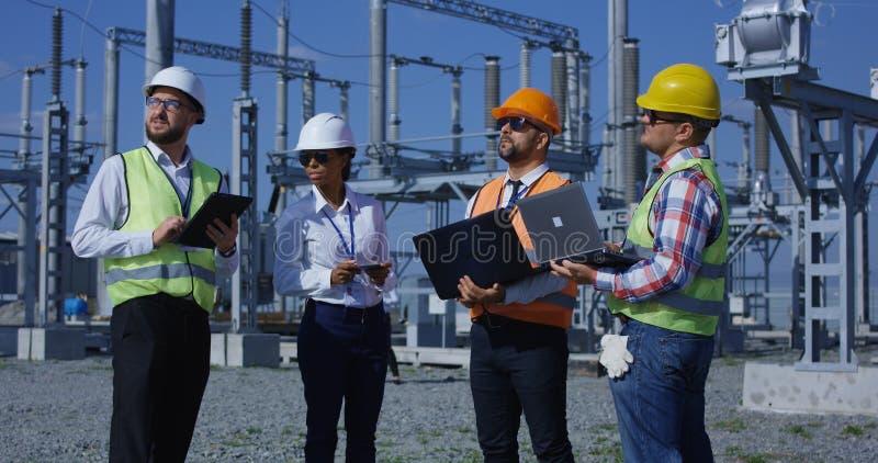 Ομάδα διαφορετικών εργαζομένων στις ηλιακές εγκαταστάσεις με τις συσκευές στοκ εικόνες με δικαίωμα ελεύθερης χρήσης