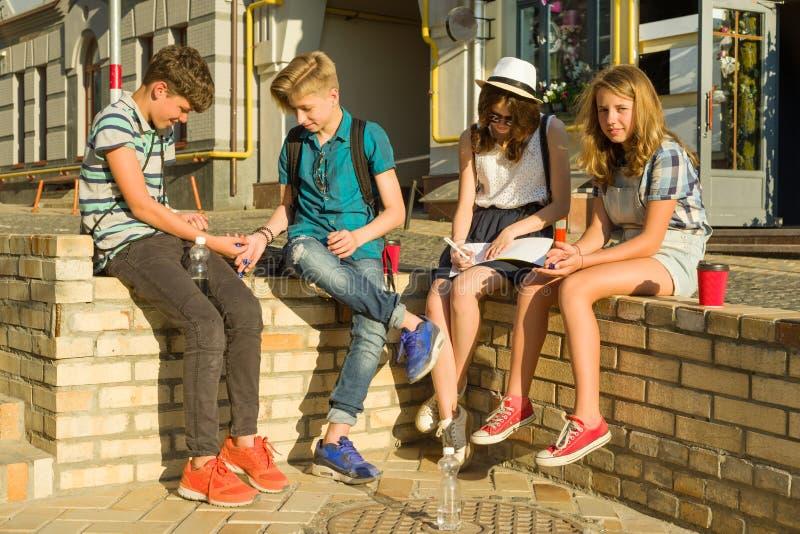 Ομάδα επικοινωνίας και αναψυχής 4 εφήβων παιδιών Οι φίλοι παίζουν ένα επιτραπέζιο παιχνίδι, η ρίψη χωρίζει σε τετράγωνα στοκ εικόνα