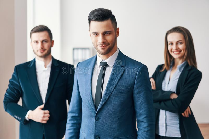 Ομάδα επιτυχούς επιχειρησιακής ομάδας και όμορφου ηγέτη τους στο μέτωπο στοκ εικόνα