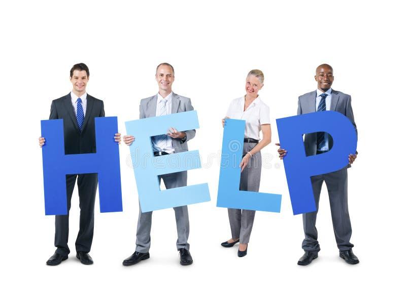 Ομάδα επιχειρηματιών που κρατούν τη βοήθεια αλφάβητου στοκ φωτογραφία