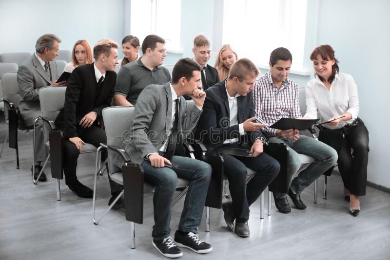 Ομάδα επιχειρηματιών στη formalwear συνεδρίαση στις καρέκλες στη αίθουσα συνδιαλέξεων στοκ εικόνες