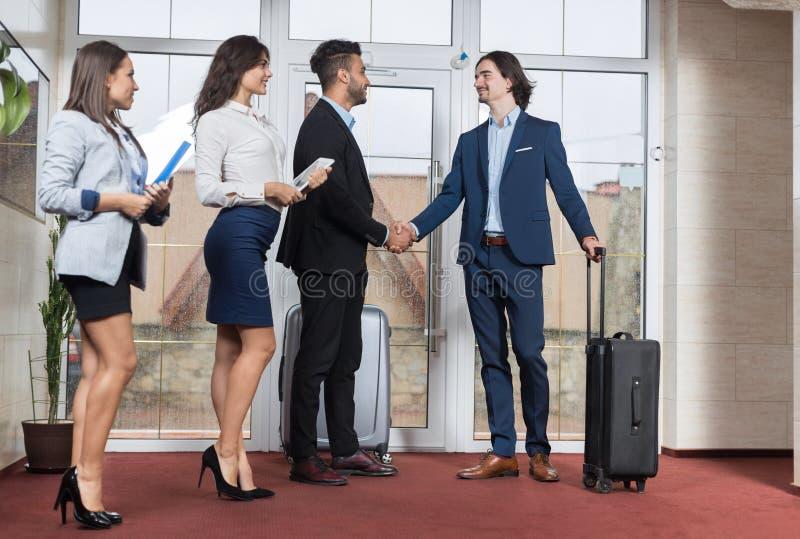 Ομάδα επιχειρηματιών συνεδρίασης των ρεσεψιονίστ ξενοδοχείων στο λόμπι, χειραψία συνεδρίασης των δύο επιχειρηματιών στοκ εικόνες
