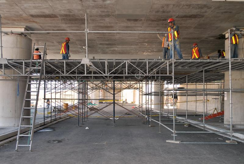 Ομάδα εργαζομένων που εργάζονται σε υλικά σκαλωσιάς σε έναν χώρο στάθμευσης στοκ εικόνα με δικαίωμα ελεύθερης χρήσης