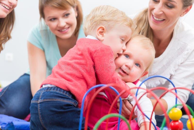 Ομάδα ευτυχών νέων μητέρων που προσέχουν το χαριτωμένο και υγιές παιχνίδι μωρών τους στοκ φωτογραφία με δικαίωμα ελεύθερης χρήσης