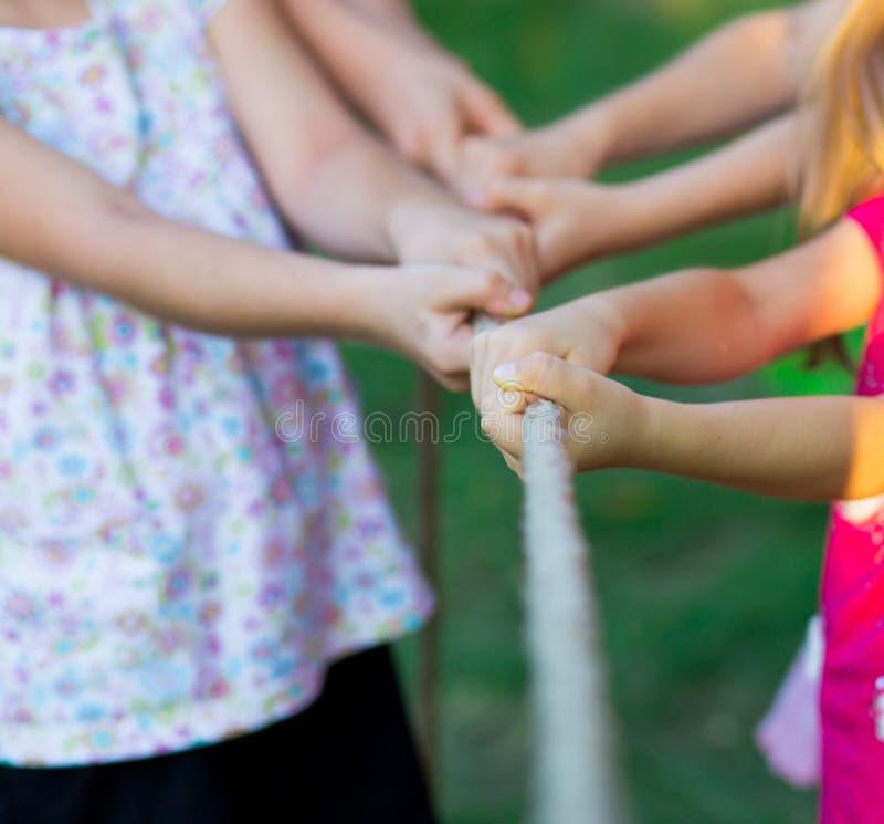 Ομάδα ευτυχών παιδιών που παίζουν τη σύγκρουση έξω στη χλόη Παιδιά που τραβούν το σχοινί στο πάρκο στοκ φωτογραφία με δικαίωμα ελεύθερης χρήσης