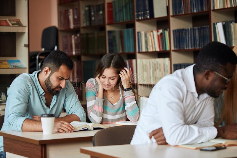 Ομάδα ευτυχών σπουδαστών που διαβάζουν τα βιβλία και που προετοιμάζονται στο διαγωνισμό στη βιβλιοθήκη στοκ φωτογραφίες