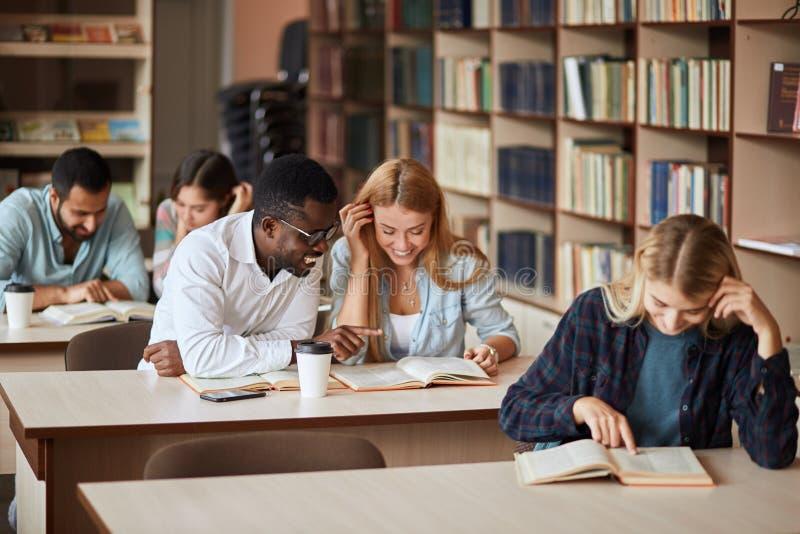 Ομάδα ευτυχών σπουδαστών που διαβάζουν τα βιβλία και που προετοιμάζονται στο διαγωνισμό στη βιβλιοθήκη στοκ εικόνες