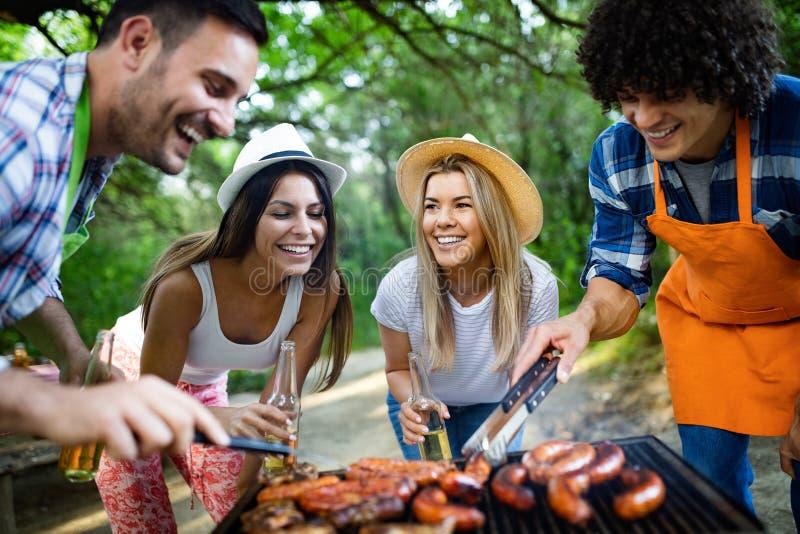 Ομάδα ευτυχών φίλων που έχουν ένα κόμμα σχαρών στη φύση στοκ φωτογραφίες