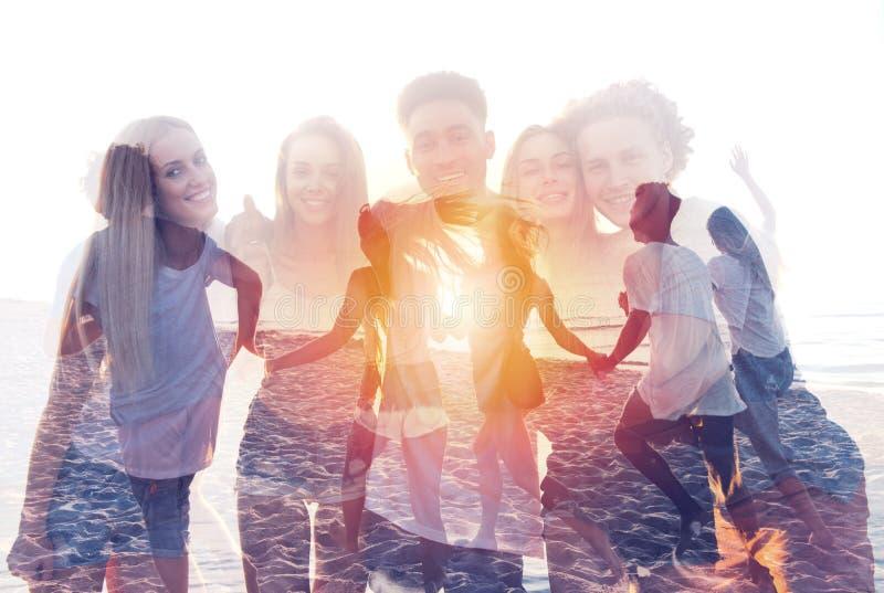 Ομάδα ευτυχών φίλων που έχουν τη διασκέδαση στην ωκεάνια παραλία διπλή έκθεση στοκ εικόνες