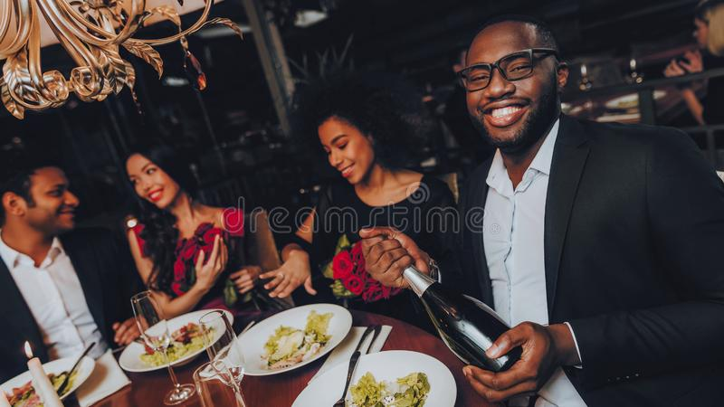 Ομάδα ευτυχών φίλων που συναντούν και που έχουν το γεύμα στοκ εικόνα