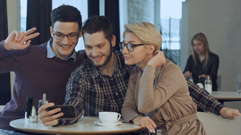 Ομάδα ευτυχών χαμογελώντας ανθρώπων που παίρνουν ένα μόνος-πορτρέτο σε έναν καφέ ενώ έχοντας ένα κενό στοκ εικόνες με δικαίωμα ελεύθερης χρήσης