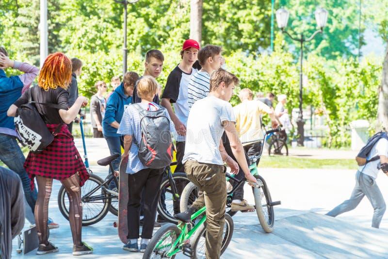 Ομάδα εφήβων με τα ποδήλατα στο πάρκο στο ποδηλατοδρόμιο στοκ φωτογραφία