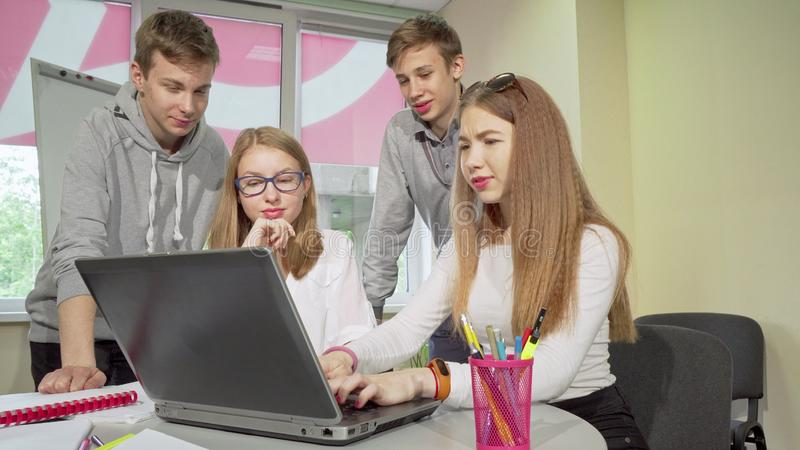 Ομάδα εφήβων που συζητούν για την ανάθεση, που σπουδάζουν μαζί στο σχολείο στοκ φωτογραφία με δικαίωμα ελεύθερης χρήσης
