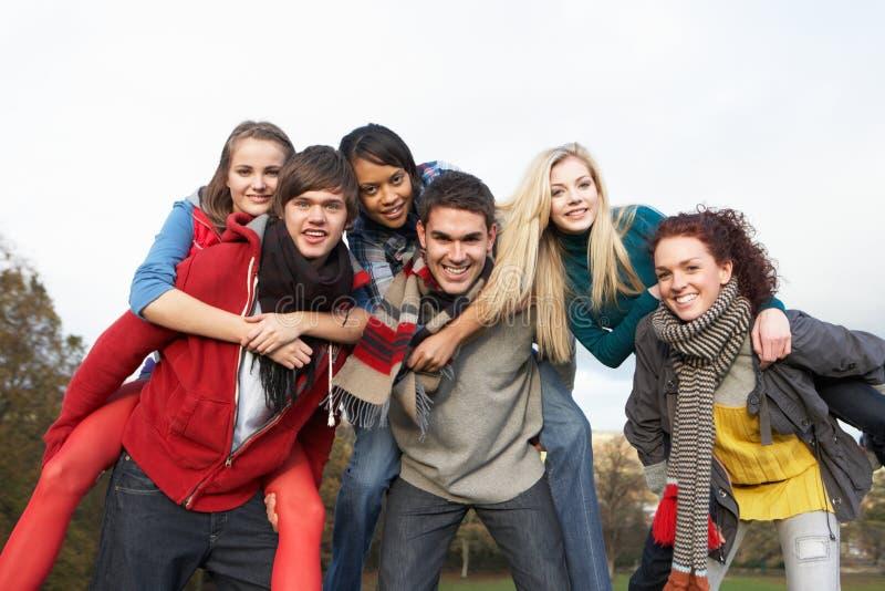 Ομάδα εφηβικών φίλων που έχουν τους γύρους σηκωήσουν στην πλάτη στοκ εικόνα