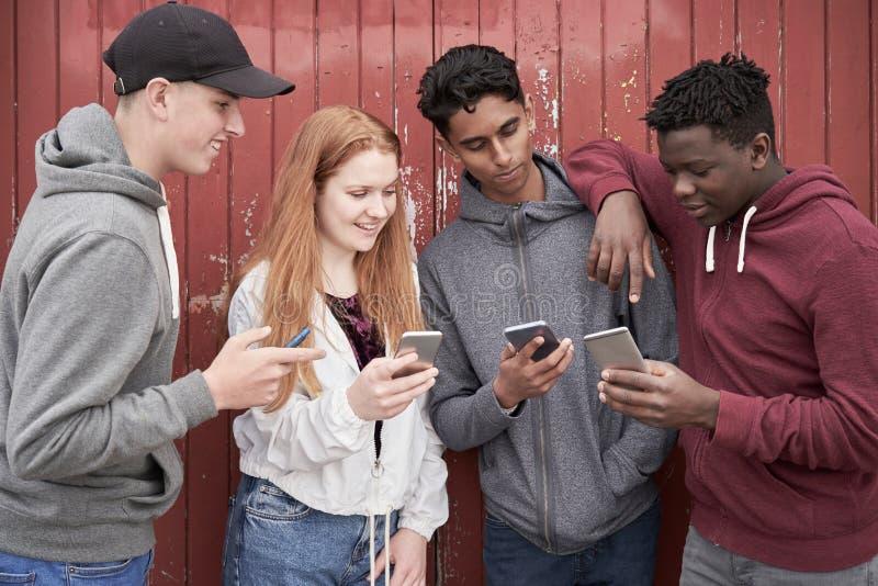Ομάδα εφηβικών φίλων που εξετάζουν τα κινητά τηλέφωνα στην αστική ρύθμιση στοκ εικόνα