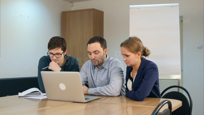 Ομάδα θετικών εύθυμων σπουδαστών χρησιμοποιώντας το lap-top και κάνοντας την εργασία μαζί στην τάξη στοκ φωτογραφίες